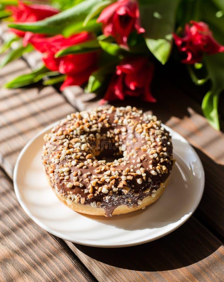Doughnut στο άσπρο πιάτο με τις τουλίπες σε ένα καφετί ξύλινο υπόβαθρο Πρόγευμα στο θερινό χρόνο στοκ εικόνα