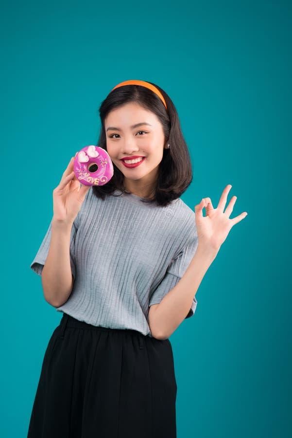 Ασιατικό κορίτσι ομορφιάς που κρατά ρόδινο doughnut Αναδρομική χαρούμενη γυναίκα με τα γλυκά, επιδόρπιο που στέκεται πέρα από το  στοκ φωτογραφίες με δικαίωμα ελεύθερης χρήσης