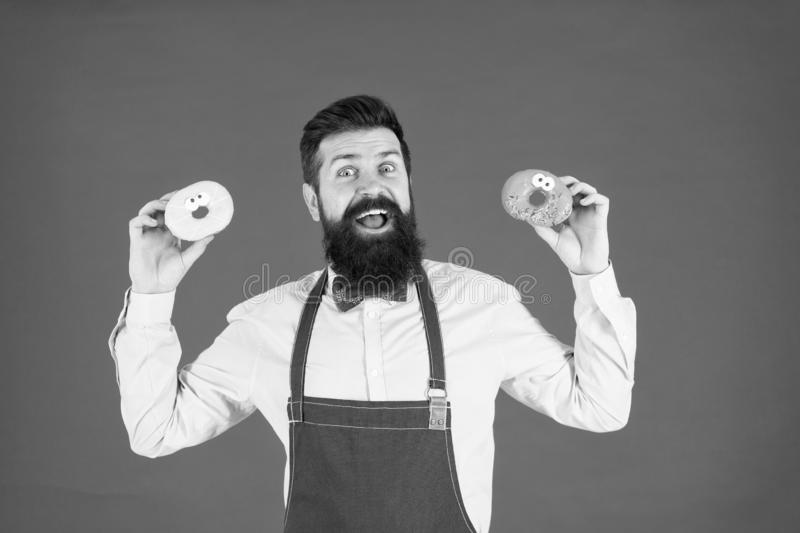 Doughnut calories. Glazed donut. Bearded well groomed man in apron selling donuts. Donut food. Baked goods. Sweets and. Cakes. Junk food. Hipster bearded baker royalty free stock photography