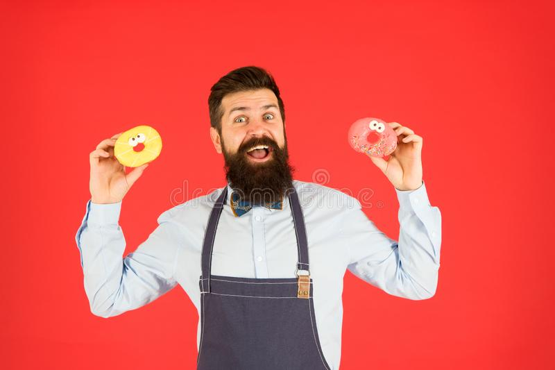 Doughnut calories. Glazed donut. Bearded well groomed man in apron selling donuts. Donut food. Baked goods. Sweets and royalty free stock images