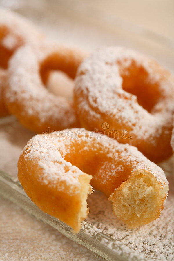 Doughnut covered icing sugar. Oval doughnut covered icing sugar on the glass plate royalty free stock image