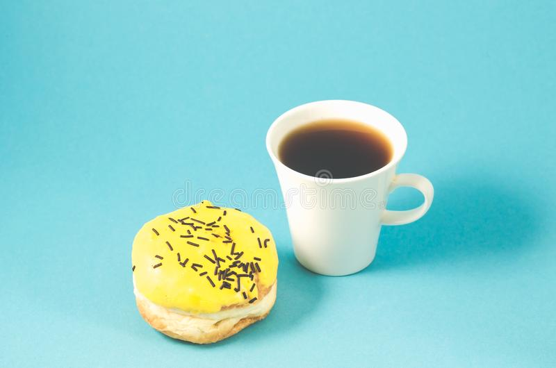 doughnut en coffe kop op blauwe die achtergrond /donut wordt en coffe kop op blauwe achtergrond, selectieve nadruk wordt geïsolee stock afbeelding