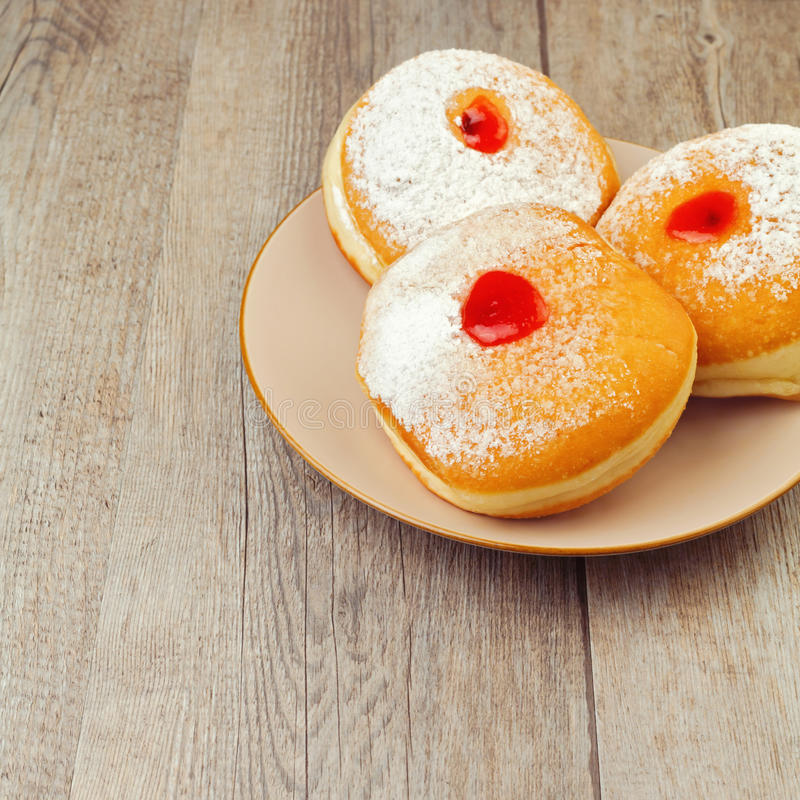 Doughnut for Jewish holiday Hanukkah on plate on wooden background stock photos