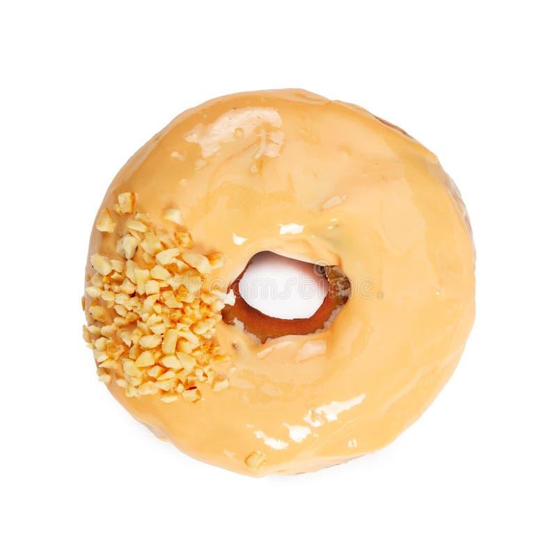 Doughnut met karamelsuikerglazuur en noten op wit worden ge?soleerd dat stock afbeeldingen