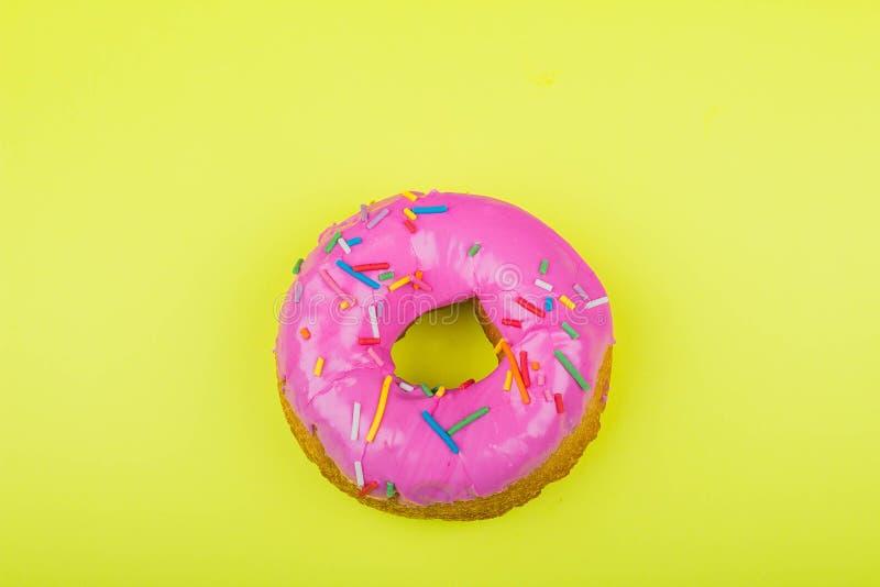 Doughnut met roze glans op een gele achtergrond stock afbeelding