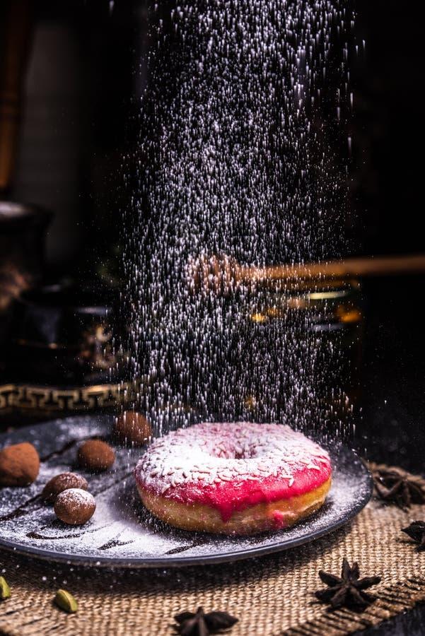 Doughnut in suikerglazuur met noten in een chocoladetruffel in een restaurant Gepoederd suikerglazuur stock afbeelding
