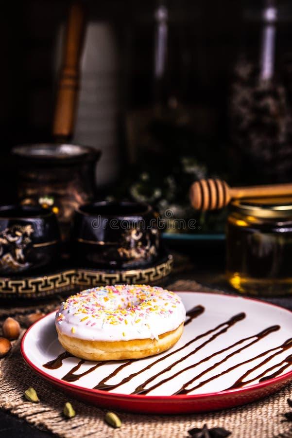 Doughnut in suikerglazuur met noten in een chocoladetruffel in een restaurant stock afbeelding