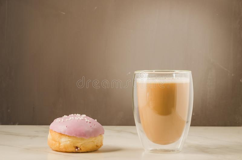 doughnut in violette glans en een cappuccinoglas /donut in violette glans en een cappuccinoglas Selectieve nadruk stock foto's