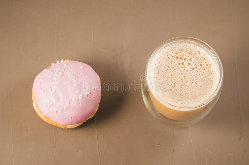 Doughnut in violette glans en een cappuccinoglas/doughnut in violette gla royalty-vrije stock afbeeldingen
