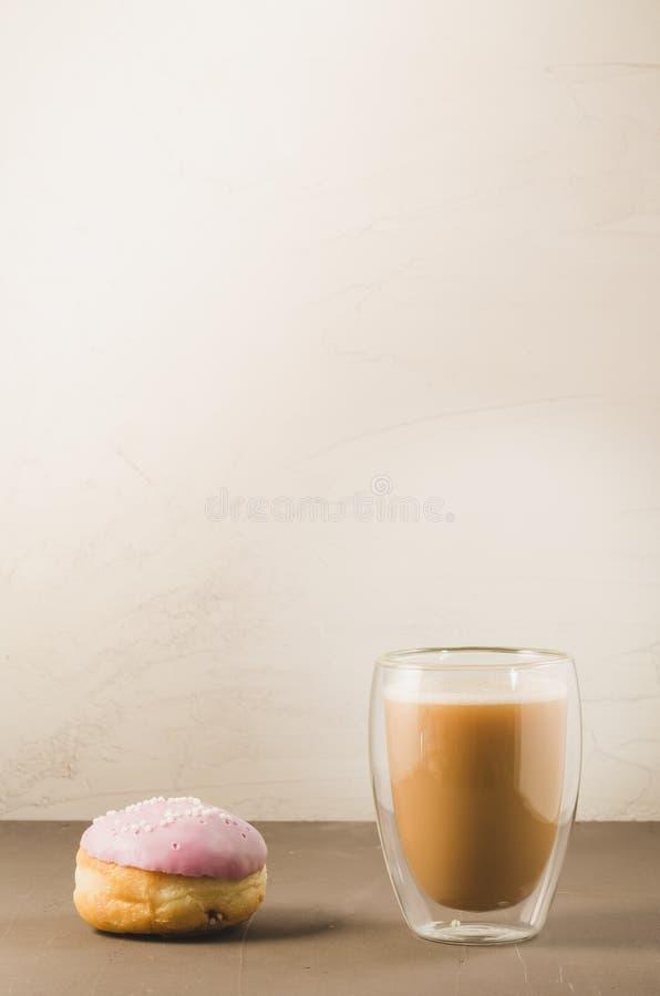 doughnut in violette glans en een cappuccinoglas/doughnut in violette glans en een cappuccinoglas op een witte achtergrond met ex stock foto's