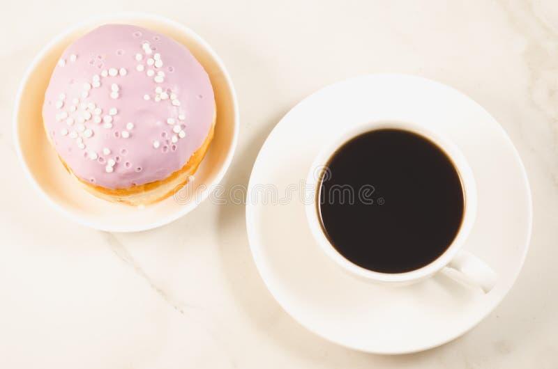 Doughnut in violette glans en een kop van zwarte koffie op een witte lijst Hoogste mening stock foto