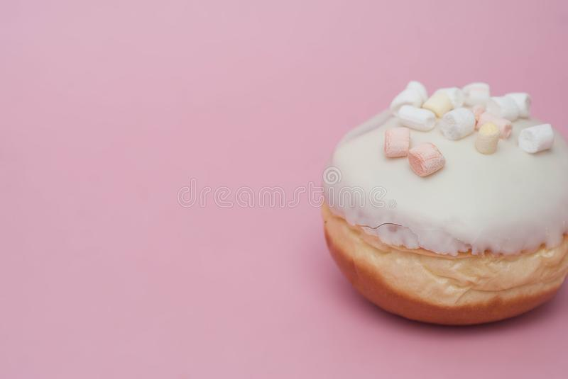 Doughnut with White Cream on Pink background. Sweet and Dessert Doughnut with copy space. royalty free stock image