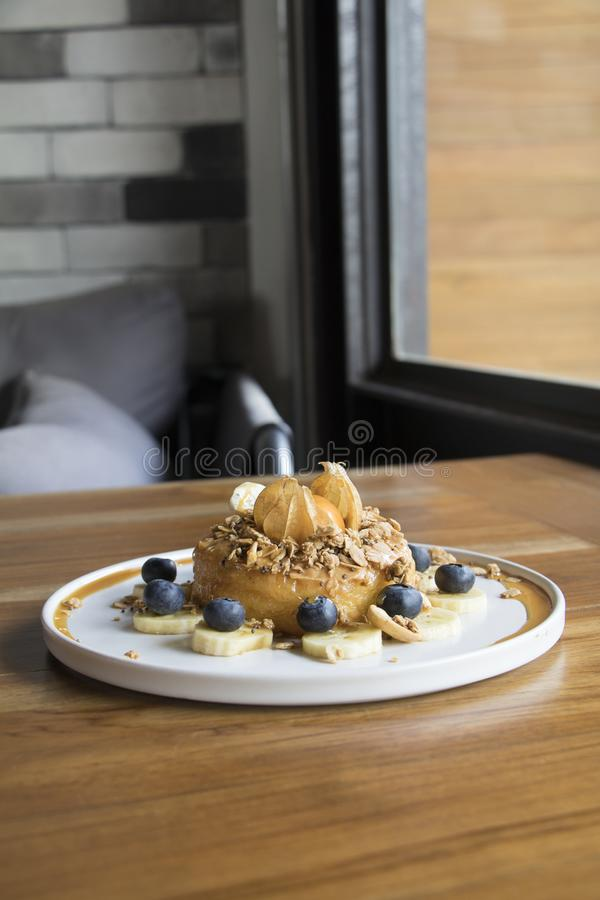 Doughnutcake met Granola, Banaan en sinaasappel op bovenkant royalty-vrije stock afbeelding