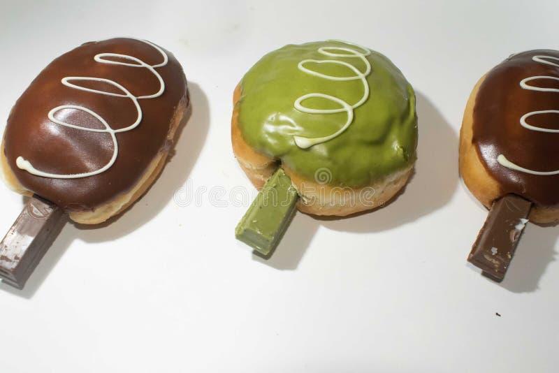 Doughnuts τριών κομματιών σε ένα άσπρο υπόβαθρο στοκ εικόνα