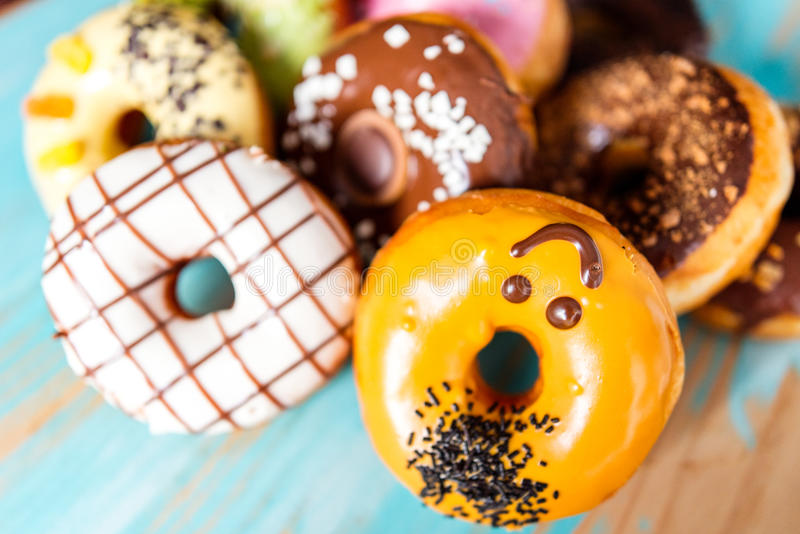 Doughnuts background. A lot of different colorful doughnuts. Chocolate, vanilla, caramel glazing and sprinkles, nuts and chocolate topping stock photo
