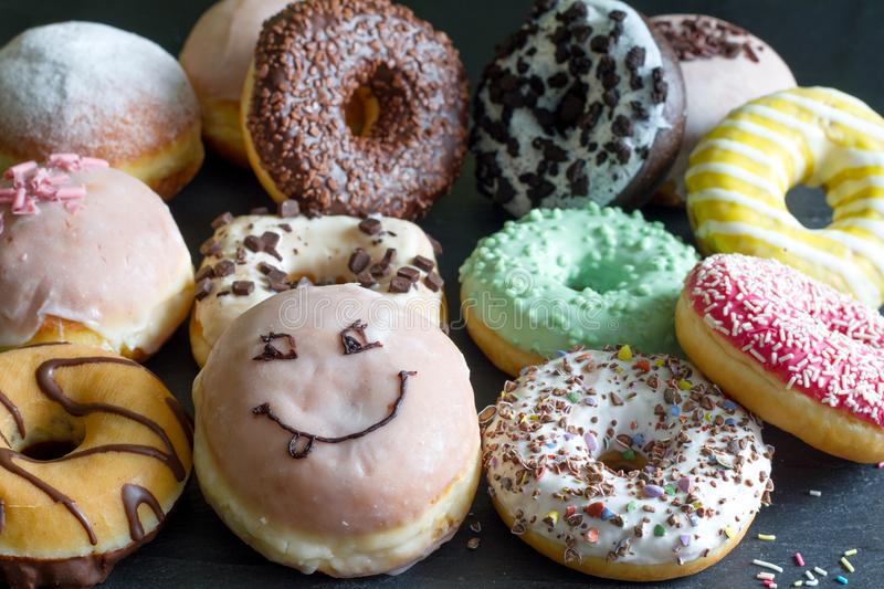 Doughnuts donuts various types of cakes abstract fat thursday concept. Closeup stock photo