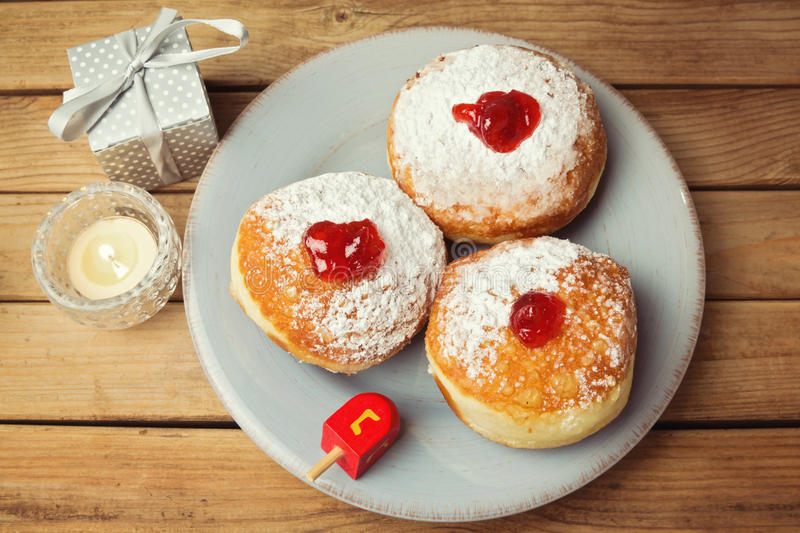 Doughnuts with jam for Jewish Holiday Hanukkah over wooden background royalty free stock photography
