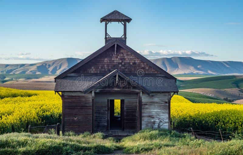 Douglas Hollow School que se sienta en campos del Canola en Oregon central fotografía de archivo