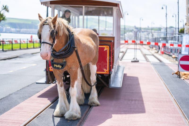 Douglas, Isle of Man, June 16, 2019. The Douglas Bay Horse Tramway on the Isle of Man runs along the seafront promenade. The Douglas Bay Horse Tramway on the stock image