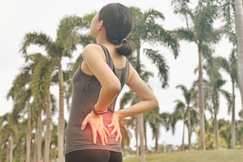 Douleur asiatique de sensation de femme sur elle de retour tout en s'exerçant image stock