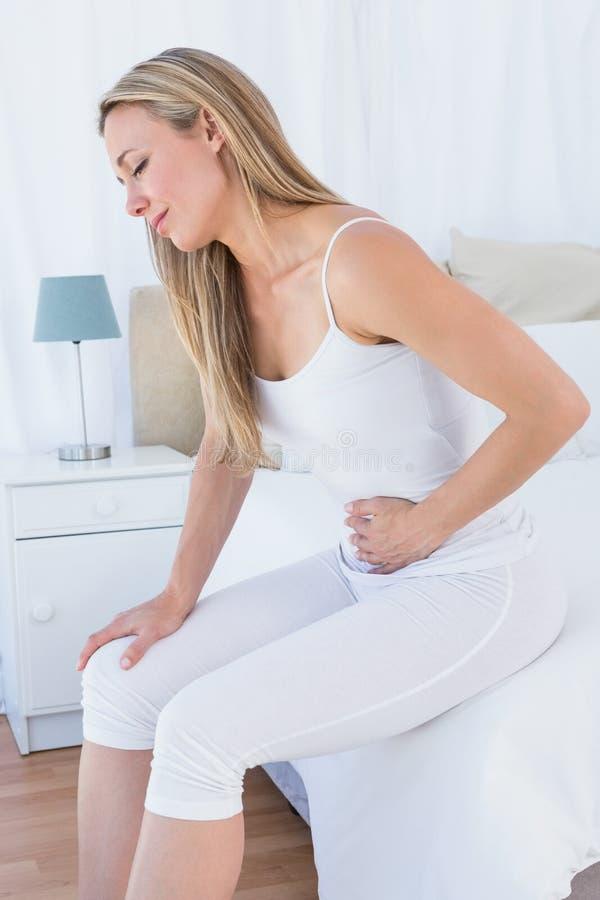 Douleur blonde bouleversée avec douleur abdominale images stock