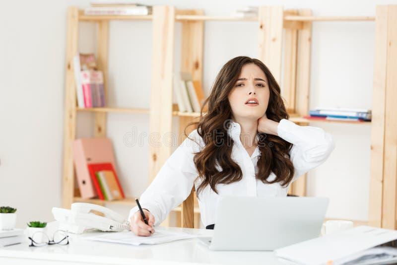 Douleur cervicale de souffrance de femme d'affaires se reposant dans une chaise tout en travaillant avec un ordinateur de bureau  images libres de droits