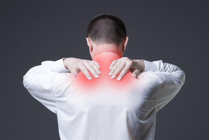 Douleur cervicale, homme avec le mal de dos sur le fond gris photos stock