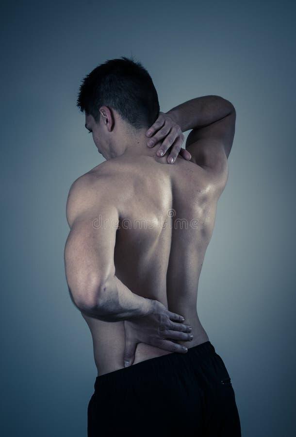 Douleur corporelle Un jeune homme fort qui souffre de douleurs au cou et au dos photo stock