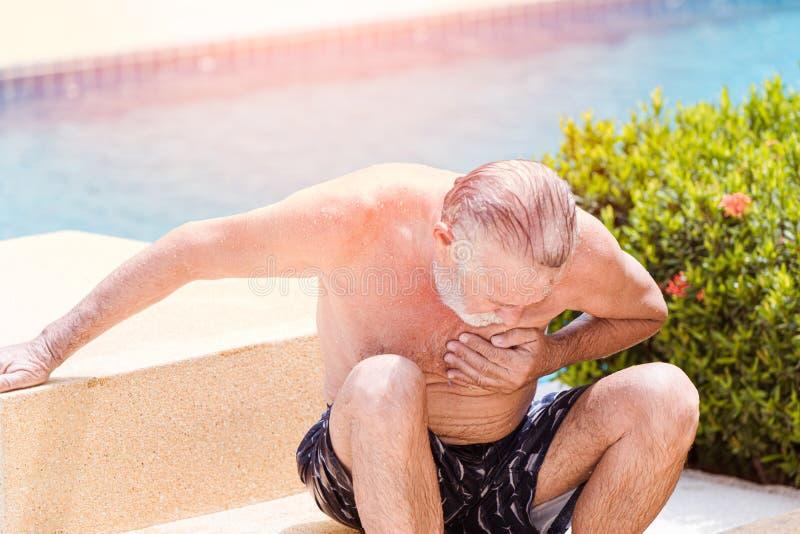 Douleur d'aîné souffrir de la crise cardiaque à la piscine dans le jour ensoleillé chaud d'été photographie stock