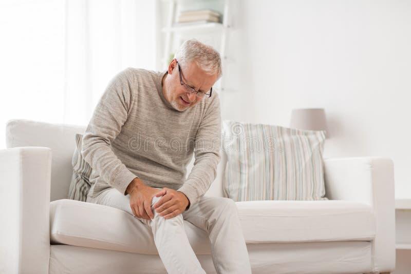 Douleur d'homme sup?rieur de mal de genou ? la maison image libre de droits