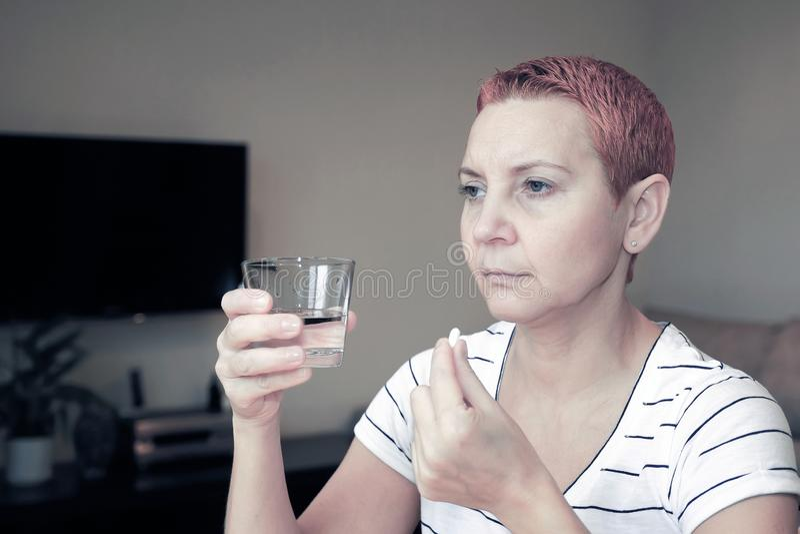 Douleur d?sagr?able Belle femme malheureuse triste s'asseyant à la table Dépression et mal de tête Prend une pilule et lave vers  images stock