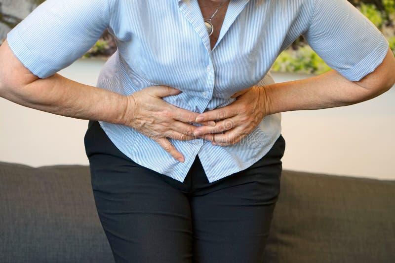 Douleur dans l'abdomen d'une femme agée images libres de droits