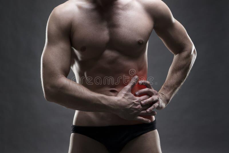 Douleur dans le côté gauche Fuselage mâle musculaire Bodybuilder beau posant sur le fond gris photographie stock libre de droits