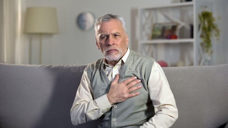 Douleur de coeur de douleur d'homme supérieur, touchant le coffre, risque d'infarctus, cardio- problèmes photo libre de droits