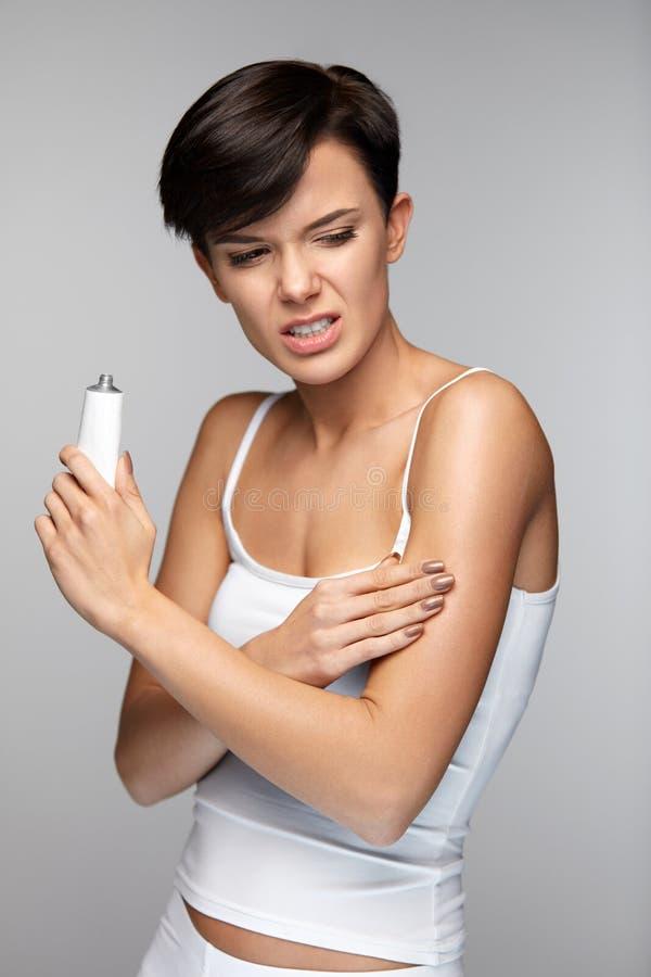 Douleur de corps Belle douleur de sentiment de femme dans des bras, appliquant la crème photographie stock