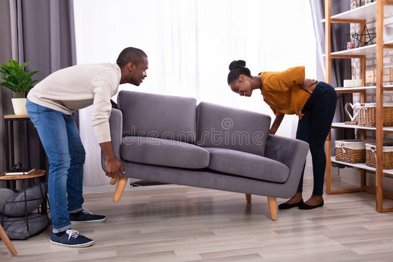 Douleur de femme des douleurs de dos tout en soulevant le sofa images stock