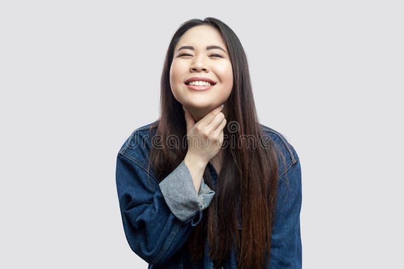 Douleur de gorge Portrait de jeune femme asiatique de brune malade dans la veste bleue occasionnelle de denim avec la position et images libres de droits