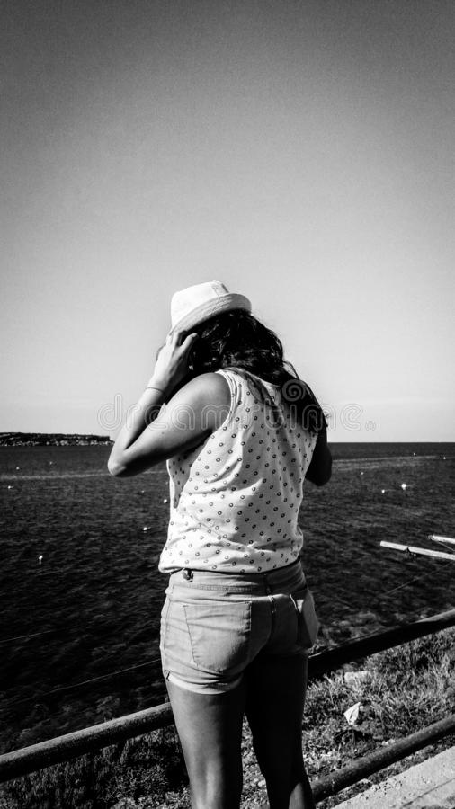 Douleur de jeune femme de la dépression fermant à clef vers le bas à la mer et cachant son visage image libre de droits