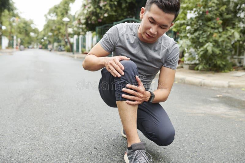 Douleur de sportif de douleur de genou images libres de droits