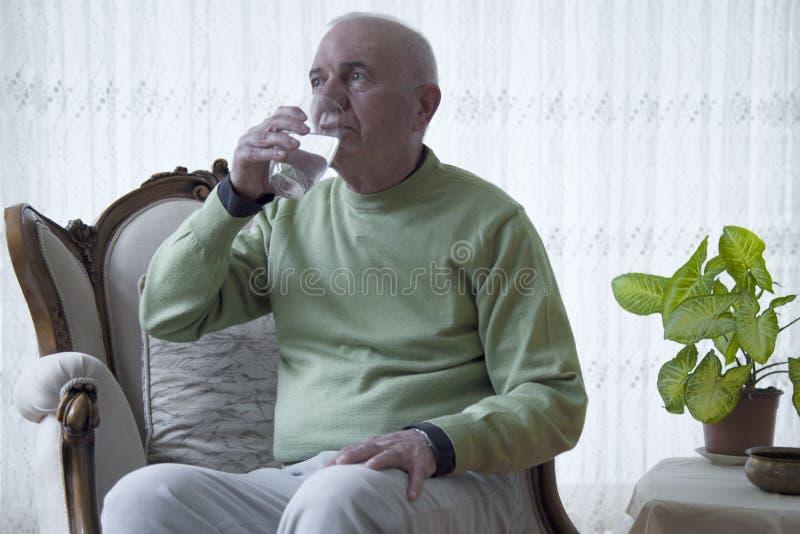 Douleur de vieil homme d'eau potable d'homme plus âgé de painPortrait dans la maison photographie stock libre de droits