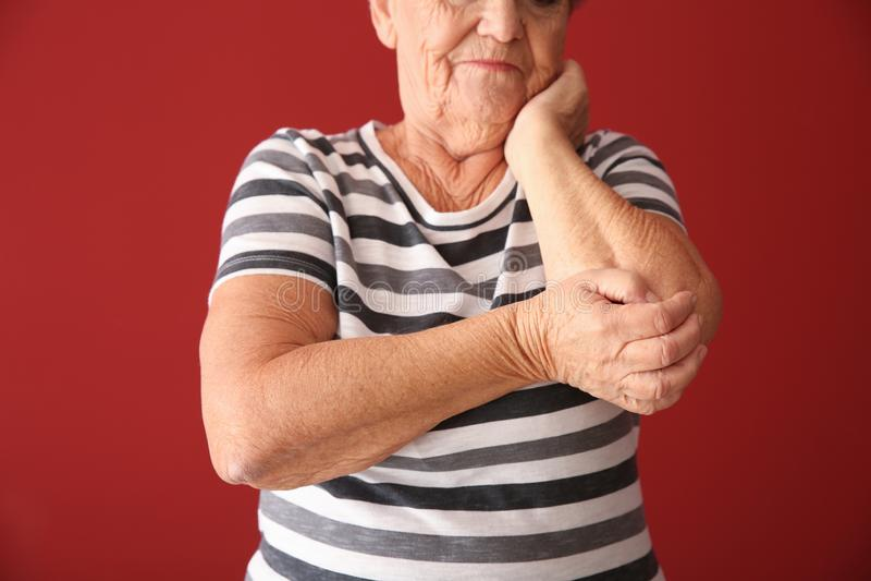 Douleur supérieure de femme de douleur dans le coude sur le fond de couleur photographie stock