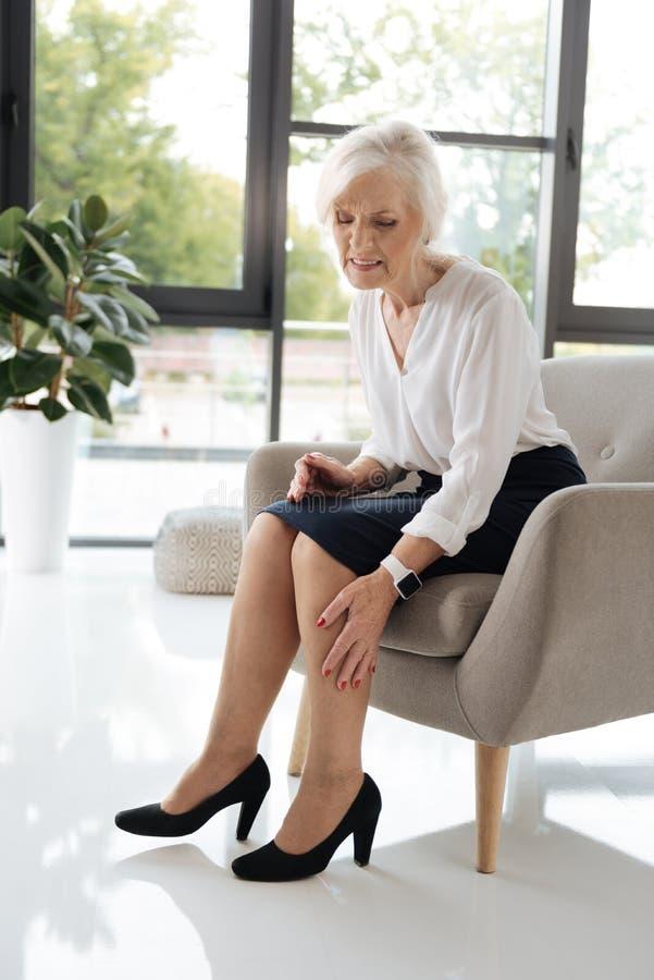 Douleur supérieure sombre de sentiment de femme dans des ses jambes images stock