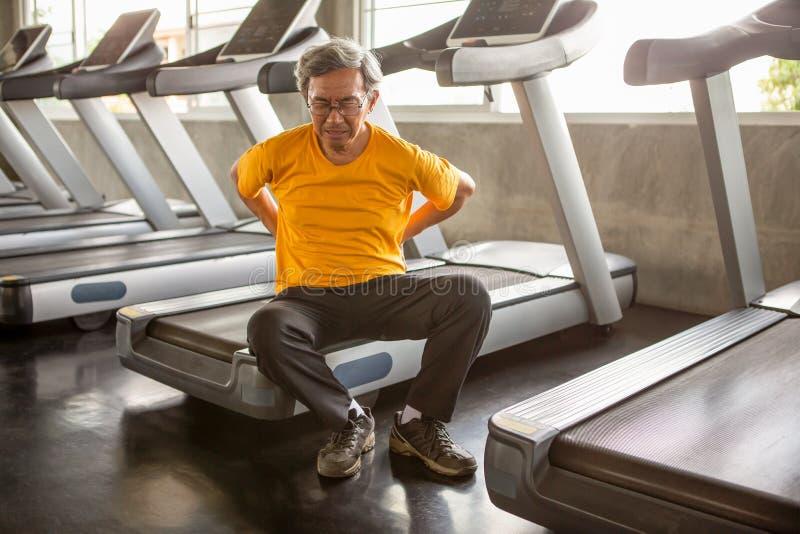 Douleurs de dos asiatiques supérieures de blessure d'homme de sport se reposant sur le tapis roulant dans le gymnase de forme phy photo libre de droits