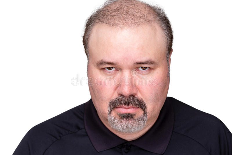 Dour angry man glowering at the camera. Dour angry middle-aged man glowering at the camera from under his brows, head and shoulders on white royalty free stock photos