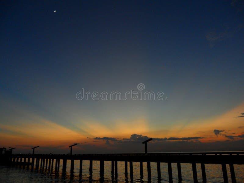 Dourado bonito após o fulgor e a lua crescente na obscuridade - céu azul sobre a ponte ao mar fotografia de stock royalty free