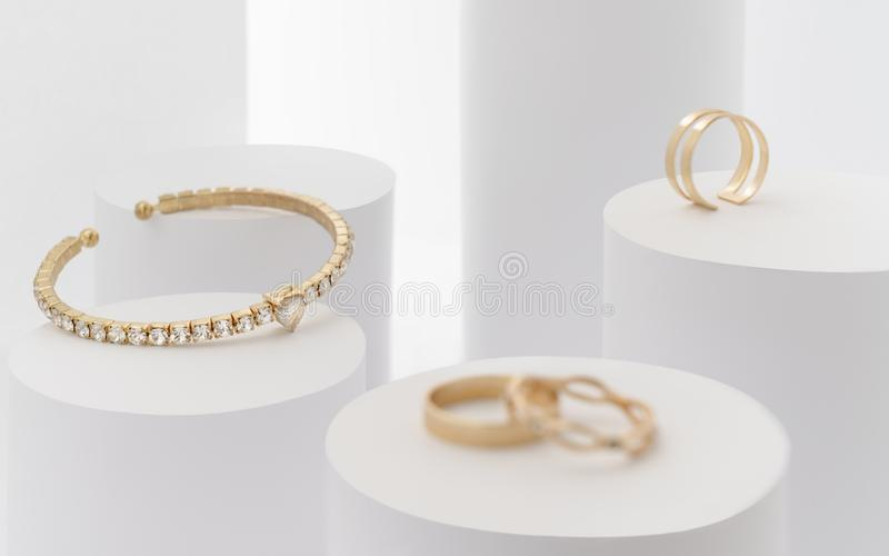 Dourado com bracelete de pedras preciosas e anéis dourados nos cilindros brancos imagens de stock