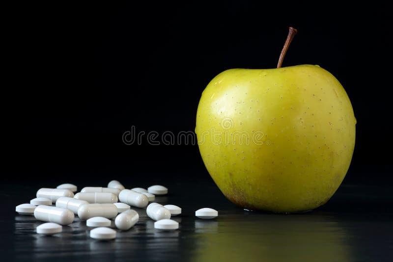 Dourado - maçã deliciosa e tabuletas e cápsulas diferentes em um fundo preto com reflexões Cuidados médicos, comer saudável e fotos de stock