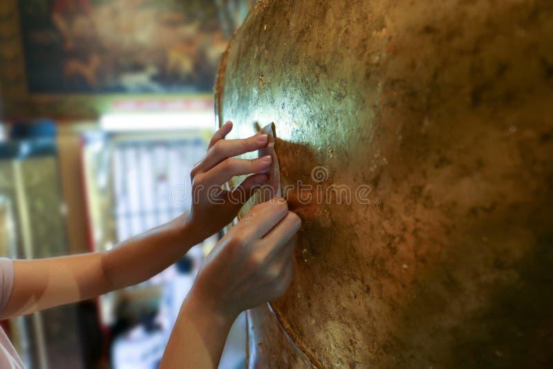 Dourando uma folha de ouro na parte de trás da estatura de buddha fotos de stock