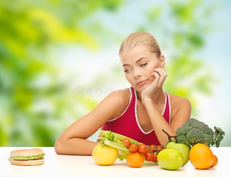 Douter de la femme avec des fruits regardant l'hamburger photos stock