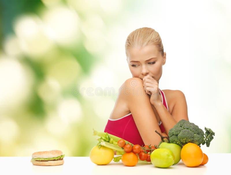 Douter de la femme avec les fruits et l'hamburger photo stock